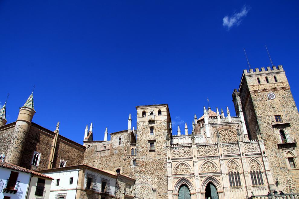 """Kloster Guadalupe in der Extremadura: """"taz"""" Das Kloster Guadalupe in der spanischen Extremadura mit seinen Zinnen und Glockentürmen ist eine Festung über der kleinen Ortschaft. Die bergige Landschaft ist im Frühsommer grün und blumenreich."""