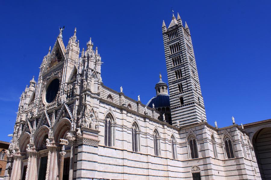Die Cattedrale di Santa Maria Assunta (besser bekannt als Dom)  ist die Hauptkirche von Siena. Aus charakteristischem schwarzem und weißem Marmor errichtet, ist sie eines der bedeutendsten architektonischen Zeugnisse der Gotik in ganz Italien. Neben der satten Pracht n der Vorderseite  ist es vor allem der in seiner Art wohl einzigartige Bodenbelag dieser Kathedrale, was mich das Hohelied singen lässt. Kunstvoll gravierte Marmorplatten sowie Intarsienarbeiten in Farbe und Schwarz-Weiß stellen Szenen mit vornehmlich biblischen Themen dar. Allein um das zu sehen, lohnt es, für den Eintritt in die Geldbörse zu greifen (unterschiedliche Preise je nach Jahreszeit und Zusatzleistungen, beginnend ab 4 Euro).